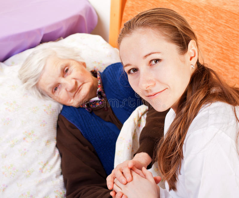Young doctor holds the elderly woman hands. Young doctor holds the old womans hands stock photo