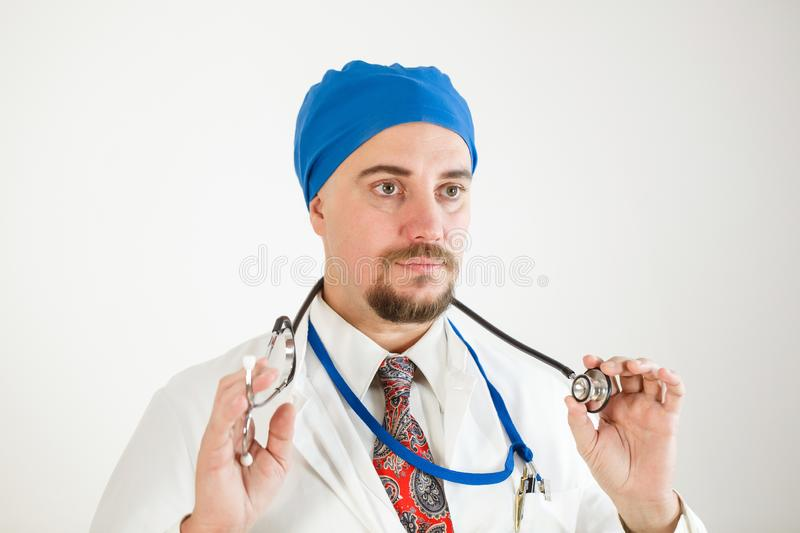 A young doctor holds a stethoscope in his hands and looks in front of him stock images