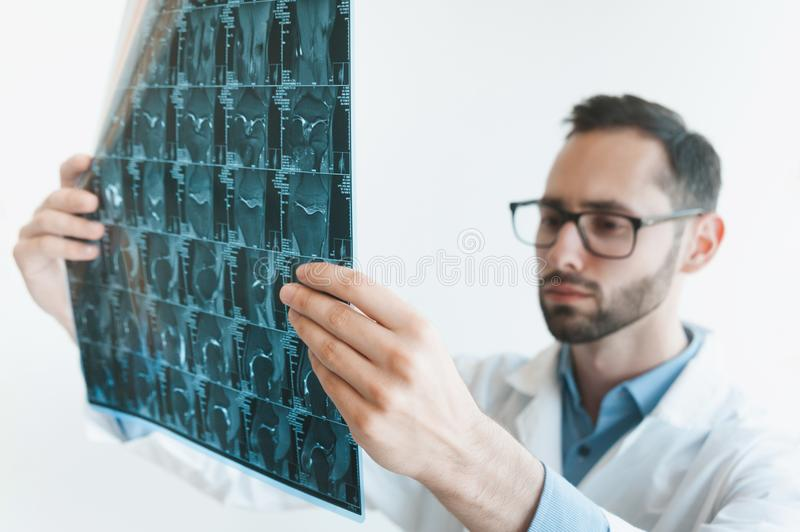 Young doctor looking at Magnetic resonance imaging shot of knee-joint. meniscus injury. Blurred stock photography