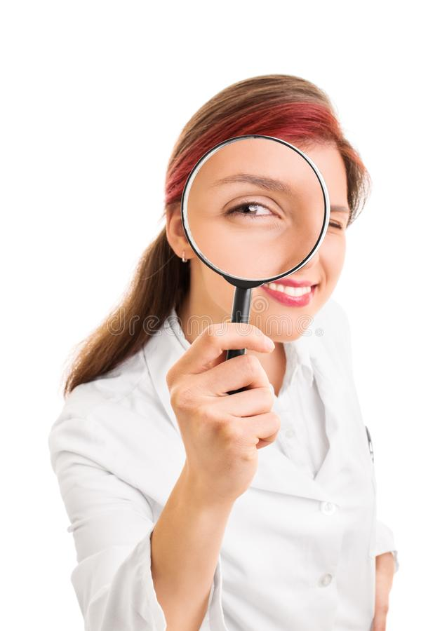 Young doctor looking through a magnifying glass. Let me take a look at you. Close up shot of a beautiful smiling young doctor looking though a magnifying glass stock photos