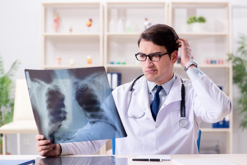 The young doctor looking at x-ray images in clinic. Young doctor looking at x-ray images in clinic royalty free stock photography