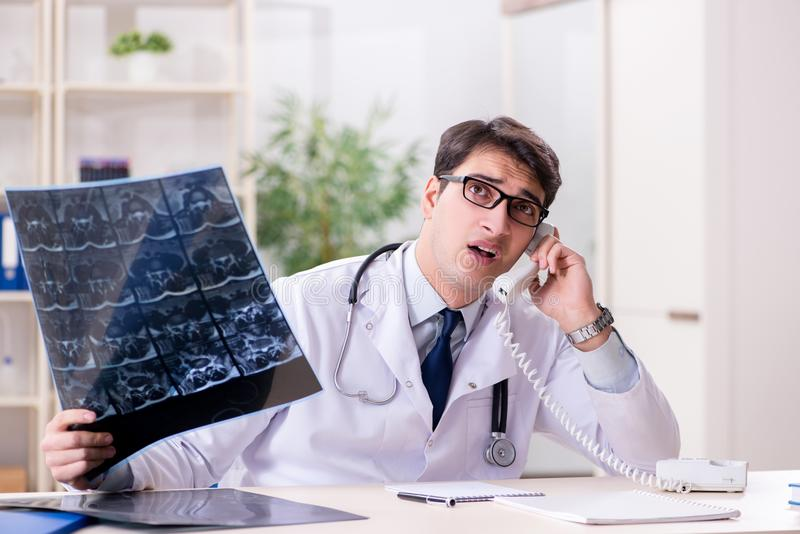 The young doctor looking at x-ray images in clinic. Young doctor looking at x-ray images in clinic royalty free stock photos