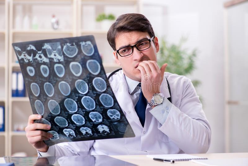 The young doctor looking at x-ray images in clinic. Young doctor looking at x-ray images in clinic stock photo