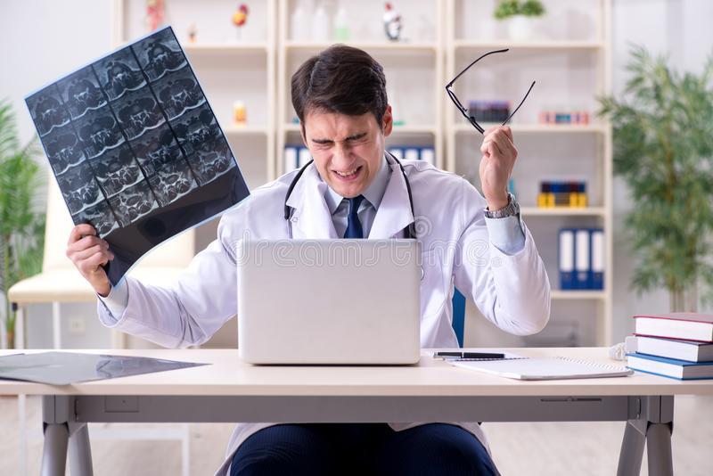 The young doctor looking at x-ray images in clinic. Young doctor looking at x-ray images in clinic stock photography