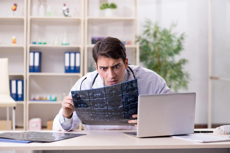 The young doctor looking at x-ray images in clinic. Young doctor looking at x-ray images in clinic royalty free stock photo