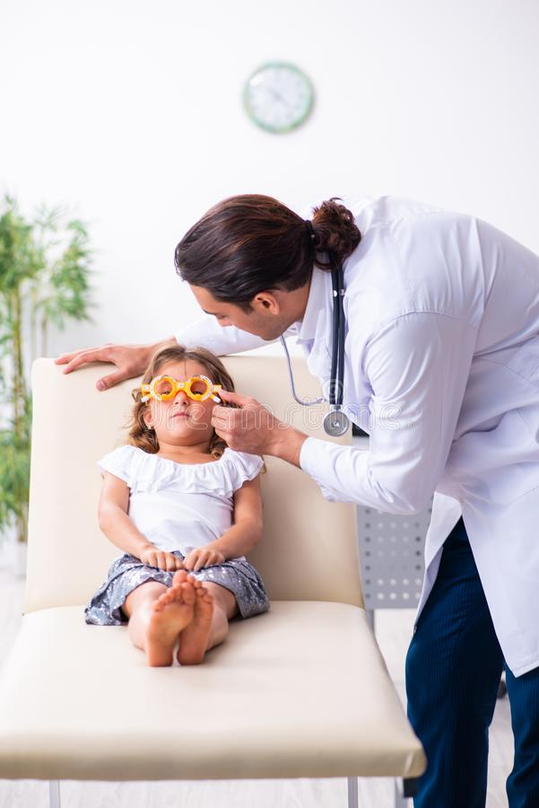 Young doctor pediatrician with small girl. The young doctor pediatrician with small girl stock photography