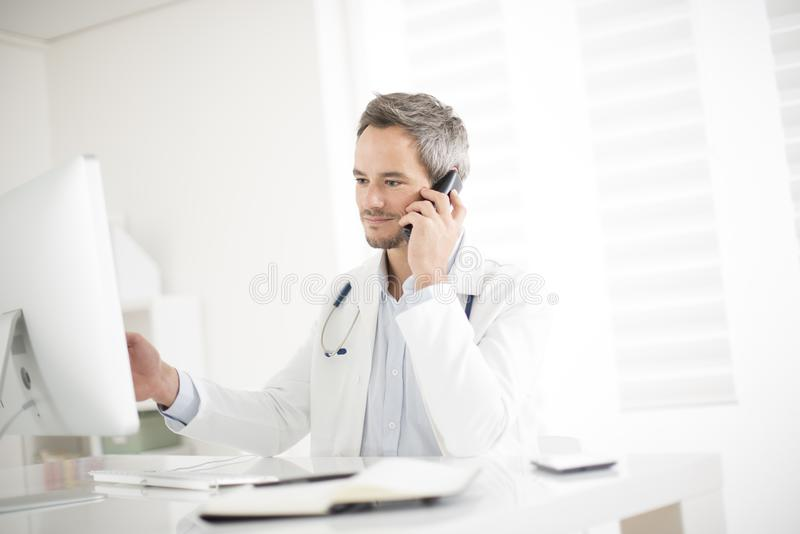 Young doctor on phone at his office. A young doctor on phone at his office stock photo