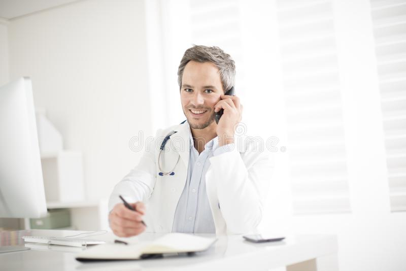 Young doctor on phone at his office. A young doctor on phone at his office royalty free stock photo