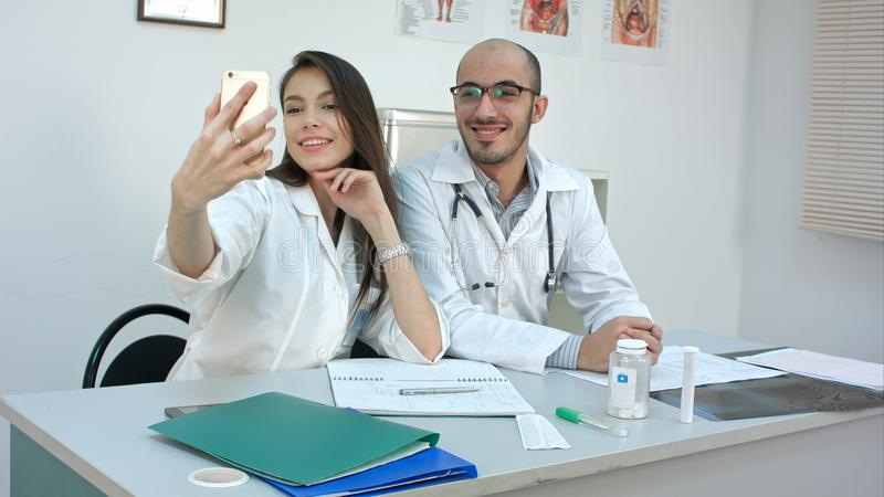 Young doctor and pretty nurse taking selfies on the phone at their desk stock photography