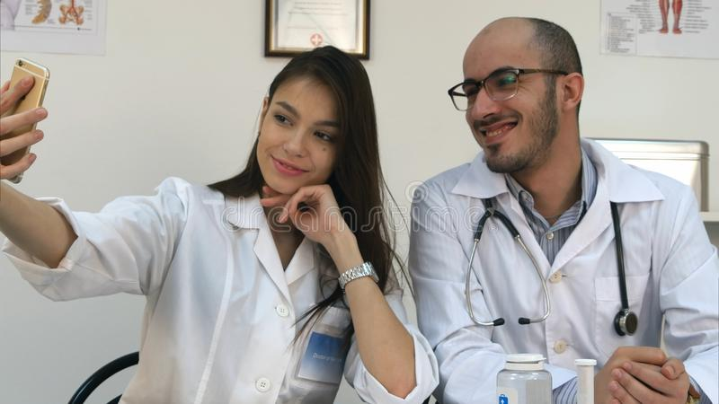 Young doctor and pretty nurse taking selfies on the phone at their workdesk royalty free stock images