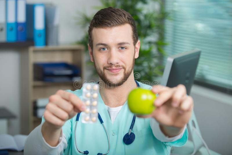Young doctor showing apple and tablets royalty free stock images