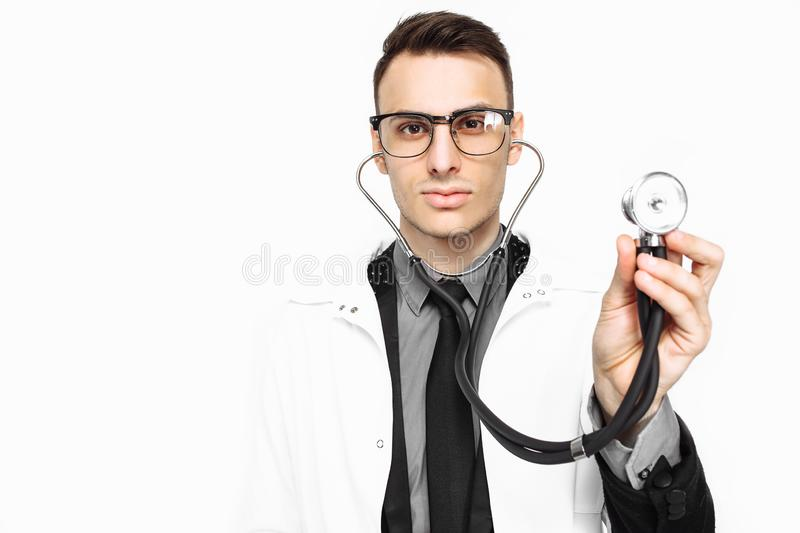 Young doctor showing a stethoscope to the survey. Close-up, hand royalty free stock images