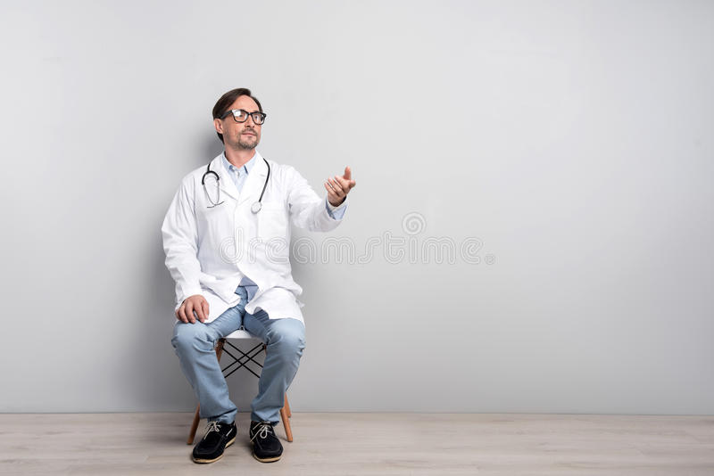 Young doctor sitting on a grey background stock photography