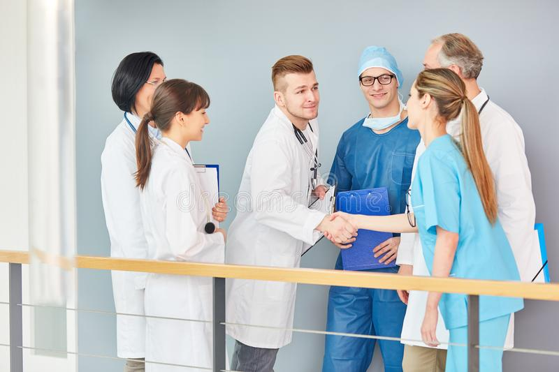 Young doctor in training shake hands with doctors royalty free stock photography