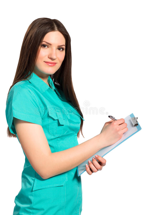 Young doctor in uniform with clipboard writing. Isolated on white background royalty free stock photo