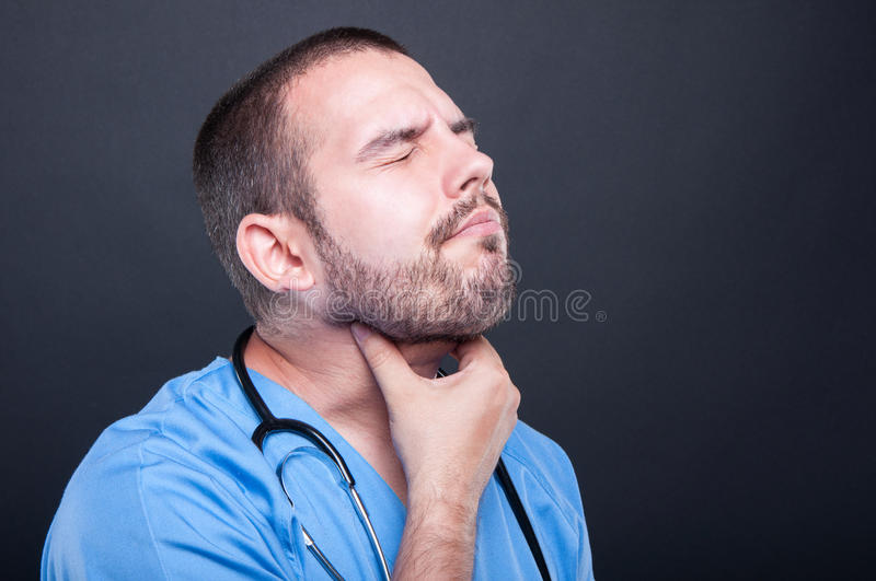 Young doctor wearing scrubs having throat pain. Or problem on black background with copy text space royalty free stock photo