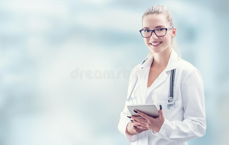 Young doctor woman smile face with tablet stethoscope and white royalty free stock photography