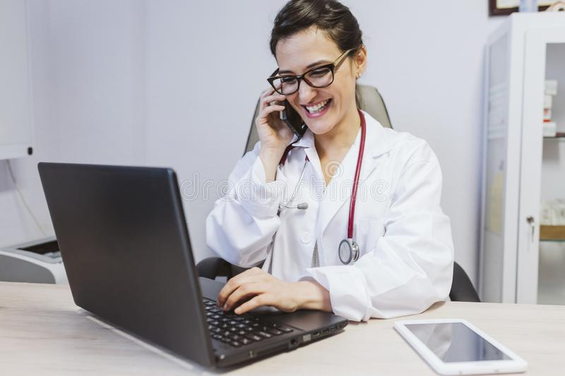 Young doctor woman working on laptop at the consult. Talking on mobile phone. Modern Medical concept indoors stock image