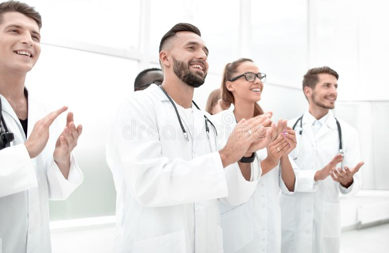 Doctors applaud at a conference. Young doctors are standing indoors and applauding looking away stock photo