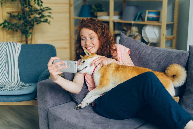 Young dog owner taking selfie with pet smiling using smartphone camera at home stock images