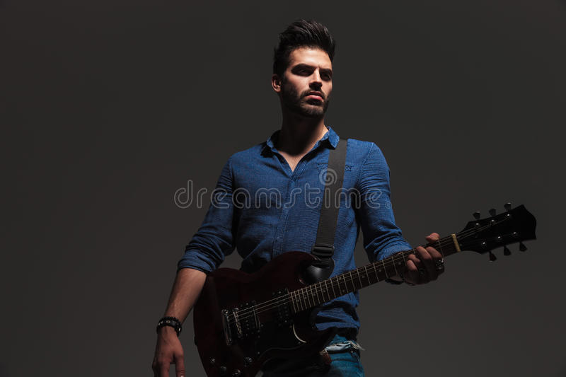 Young dramatic guitarist looking away to side while playing. Electric guitar on grey background stock photo