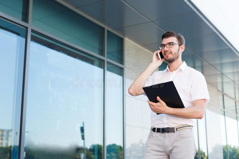 Young dreamy man with clipboard making a call outdoors stock image