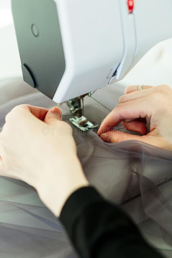 Young dressmaker woman sews clothes on sewing machine royalty free stock photography