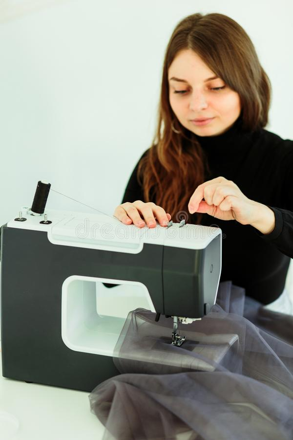 Young dressmaker woman sews clothes on sewing machine royalty free stock images
