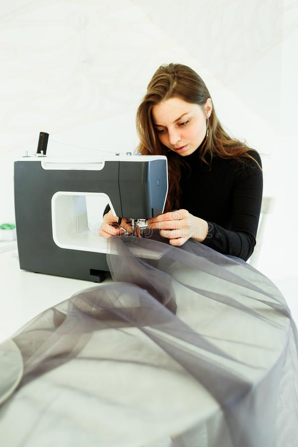 Young dressmaker woman sews clothes on sewing machine stock photo