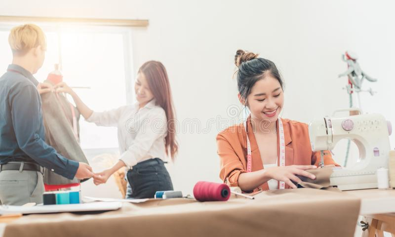 Young dressmaker woman sews clothes on sewing machine. Smiling seamstress and her hand close up in workshop. Focus on sewing. Young dressmaker women sews clothes royalty free stock photo