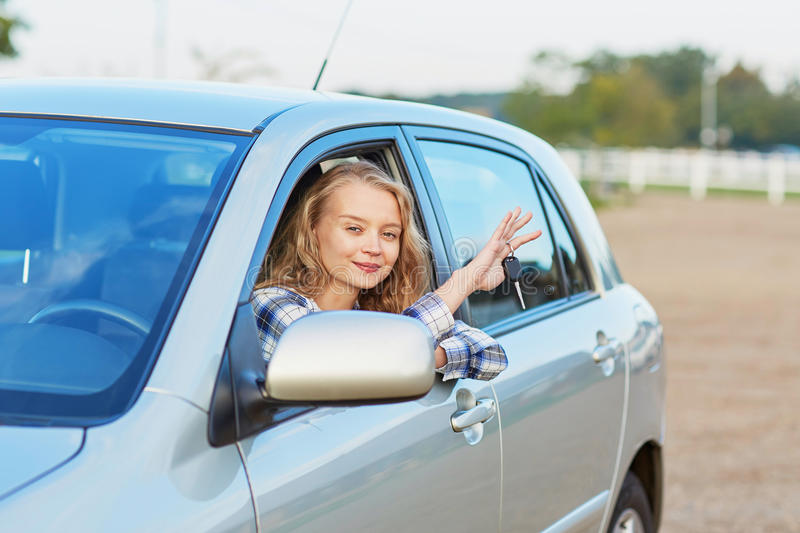 Young driver looking out of the car window holding a key. Beautiful young driver looking out of the car window holding a key stock image