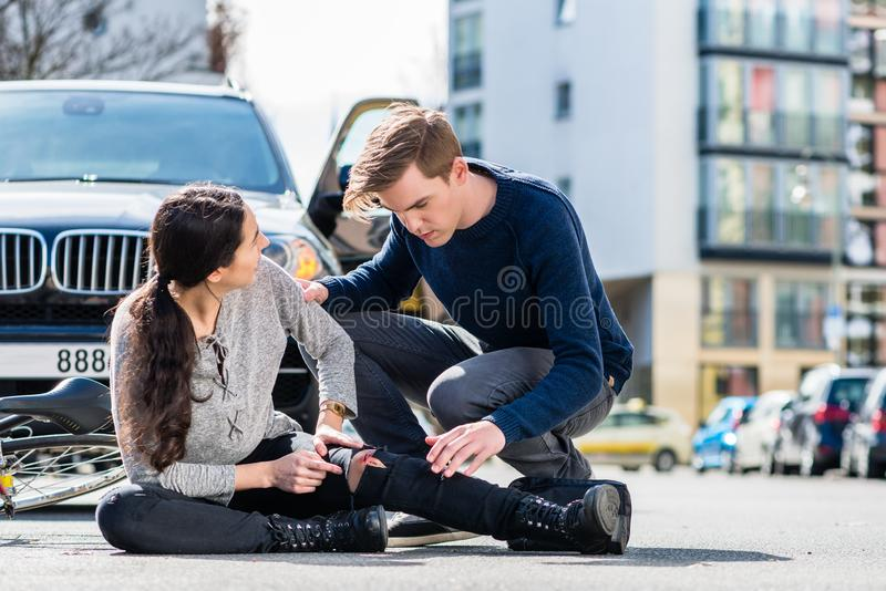 Young driver using a sterile bandage to help an injured bicyclist stock photo
