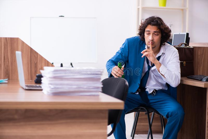 Young drunk employee in the office royalty free stock photo