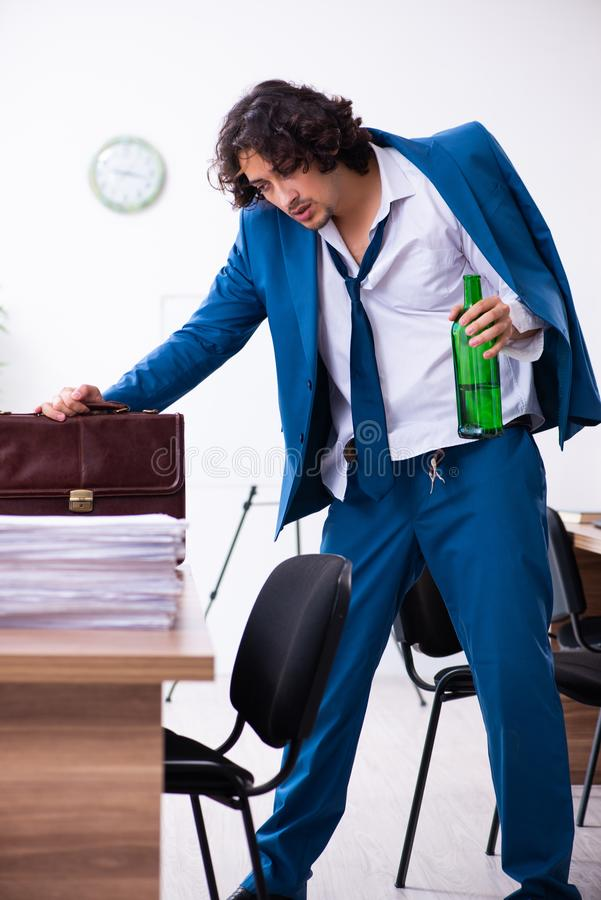 Young drunk employee in the office stock photography