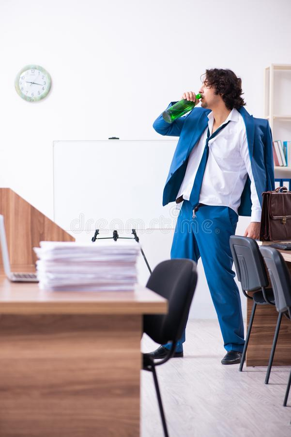 Young drunk employee in the office royalty free stock images