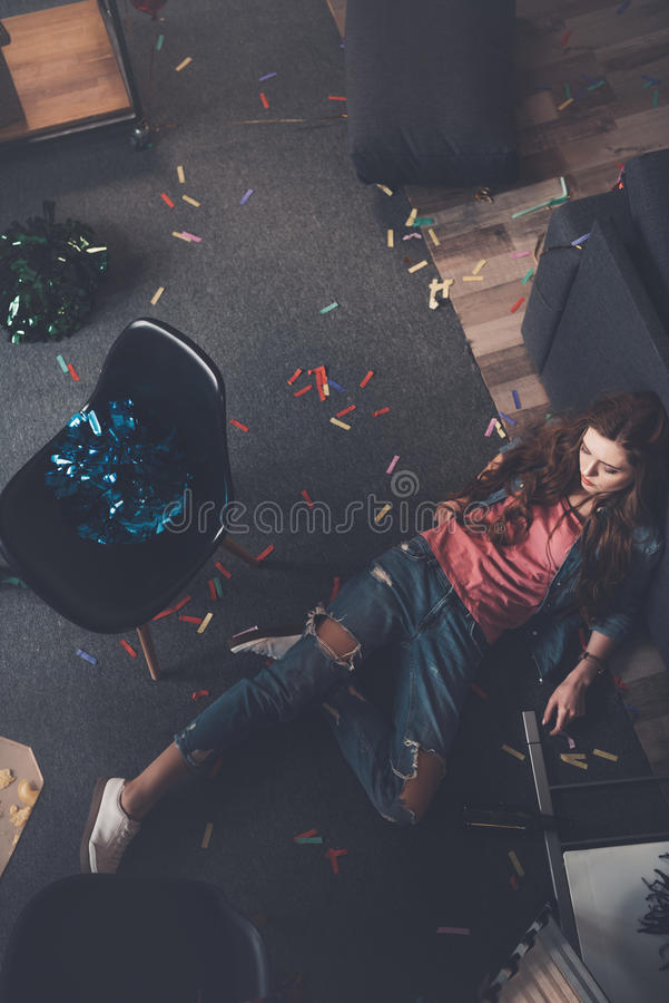 Young drunk woman lying on floor in messy room royalty free stock image