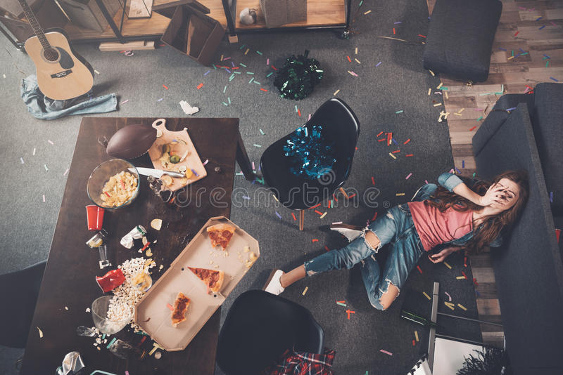 Young drunk woman lying on floor in messy room stock photography