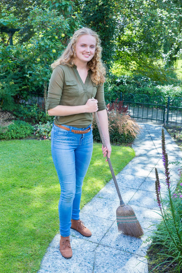 Young dutch woman sweeping garden path with wicker broom. Young caucasian teenage girl sweeping garden path with wicker broom royalty free stock photos