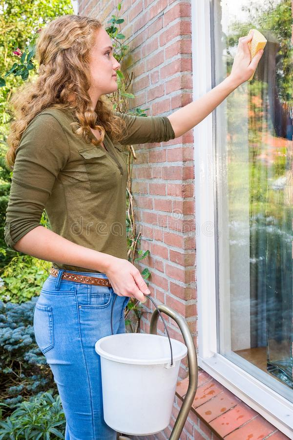 Young european woman washing house window outdoors stock images
