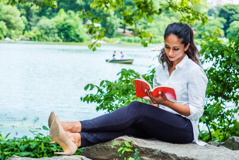 Young East Indian American Woman reading red book, relaxing at Central Park, New York. Wearing white shirt, black pants, high heels, sitting on rocks by lake royalty free stock image