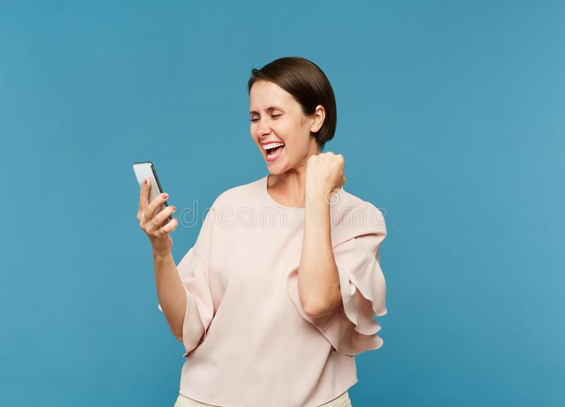 Young ecstatic female looking at smartphone screen royalty free stock photo