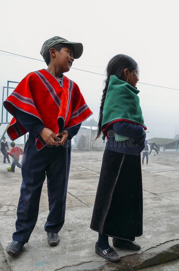 Young Ecuadorian indigenous schoolboy and schoolgirl pose for a picture at their schoolyard royalty free stock photos