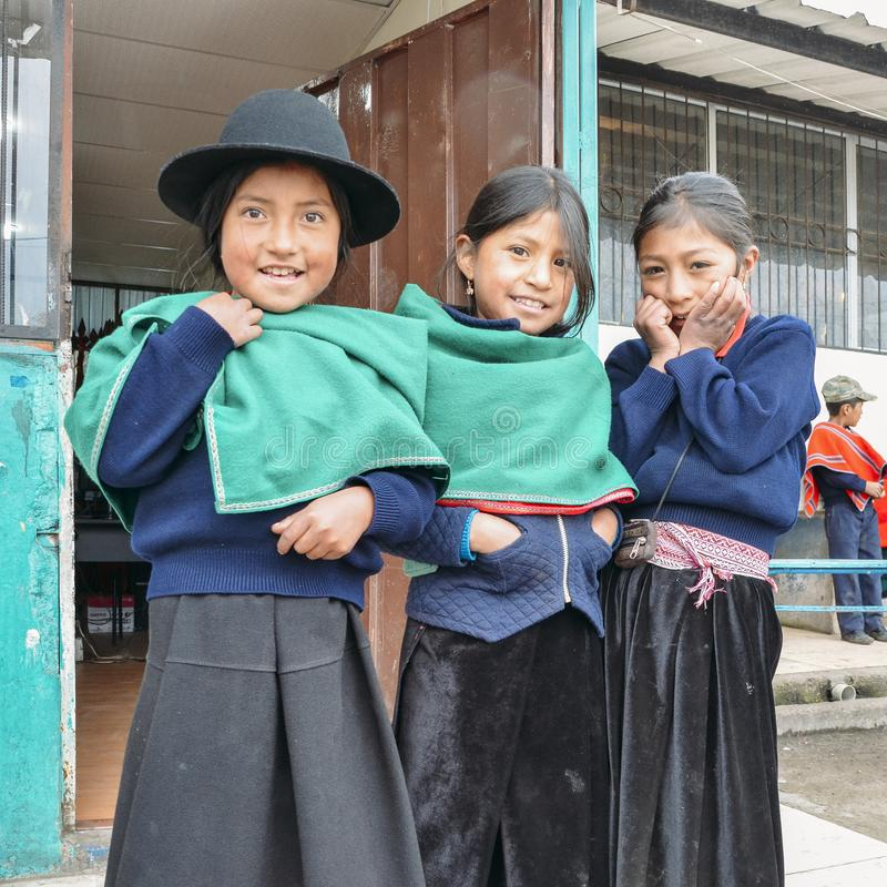 Young Ecuadorian indigenous schoolgirls pose for a picture outside their school stock image