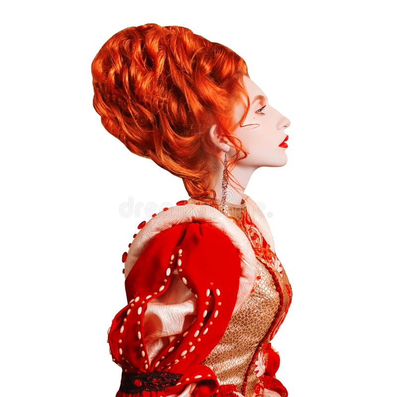 Young edwardian redhead queen with hairstyle isolated on white background. Renaissance princess with red hair isolated. Fairytale. Queen in red dress. Edwardian royalty free stock image