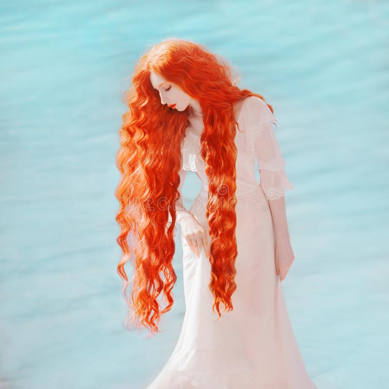 Young edwardian woman with long hair, red lips, pale skin on blue water background. Beautiful redhead model against the lake in white edwardian dress stock photos