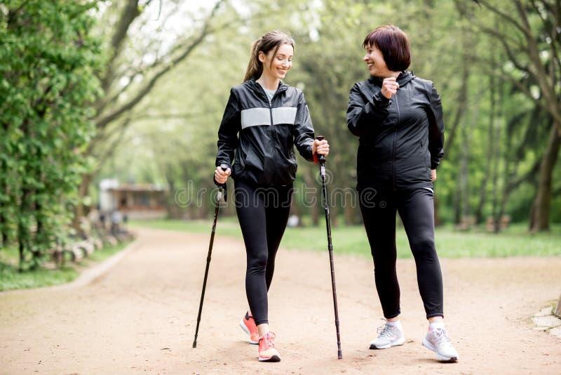 Women walking with hiking sticks in the park. Young and elder women in black sportswear walking with hiking sticks in the park royalty free stock photo