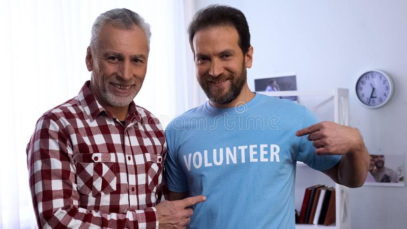 Young and elderly men showing volunteer word on t-shirt to camera, charity. Stock photo stock image