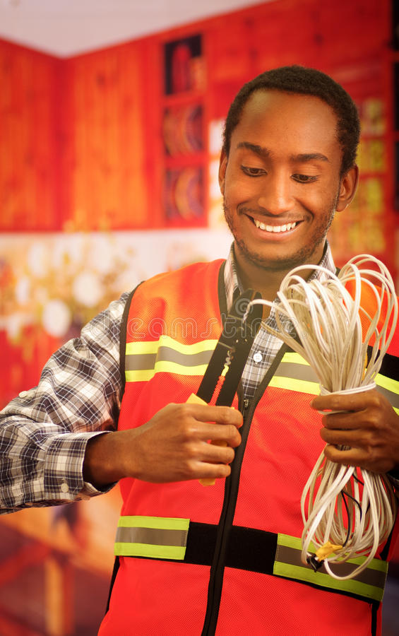 Young electrical worker wearing safety vest, holding cables and cable pliars, smiling with great positive attitude.  royalty free stock photo