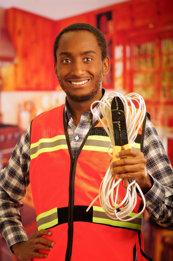 Young electrical worker wearing safety vest, holding cables and cable pliars, smiling with great positive attitude.  stock photography
