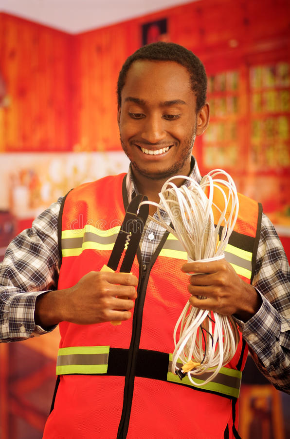 Young electrical worker wearing safety vest, holding cables and cable pliars, smiling with great positive attitude.  royalty free stock photos